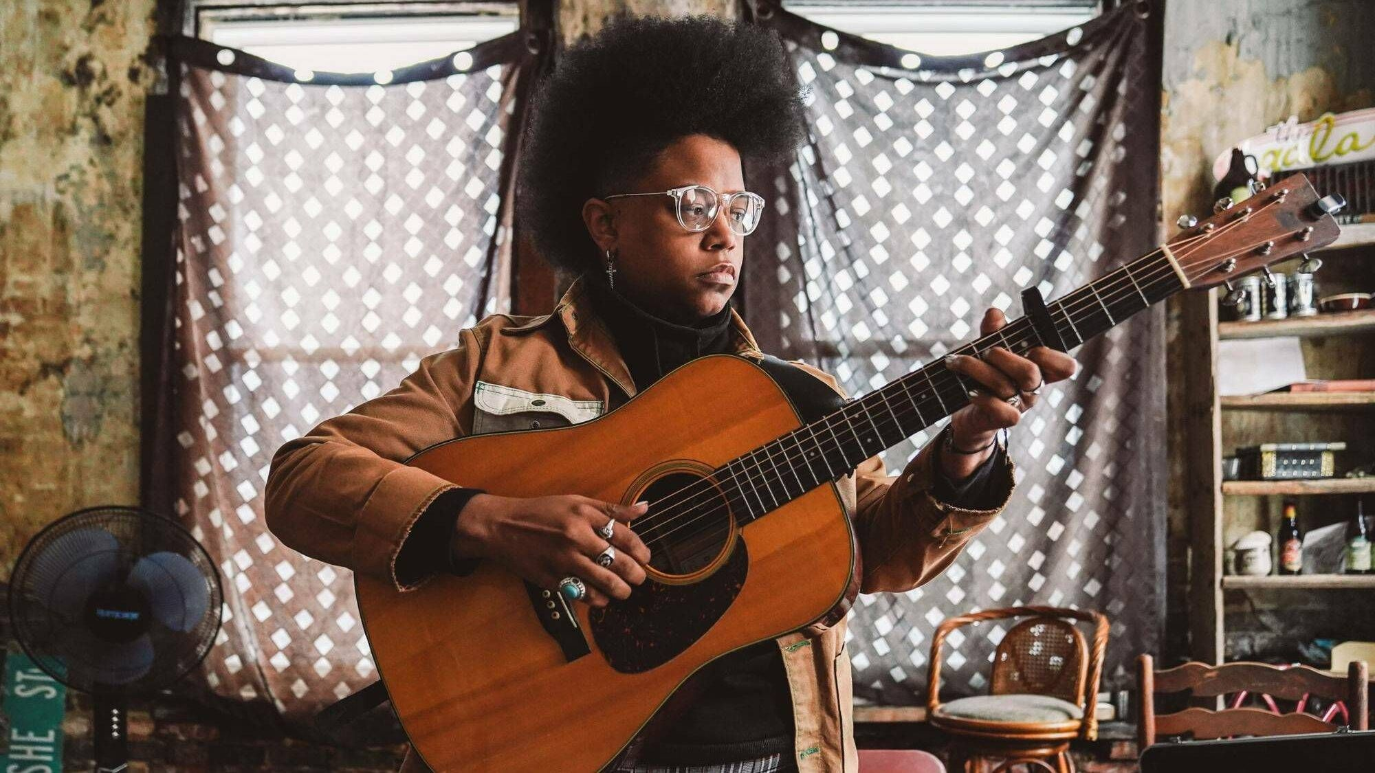 A woman plays guitar in an old apartment building, music as therapy, Rewire