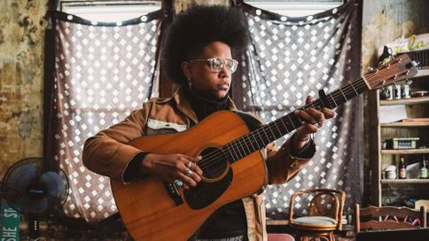 A woman plays guitar in an old apartment building. Rewire PBS Our Future Amythyst Kiah music