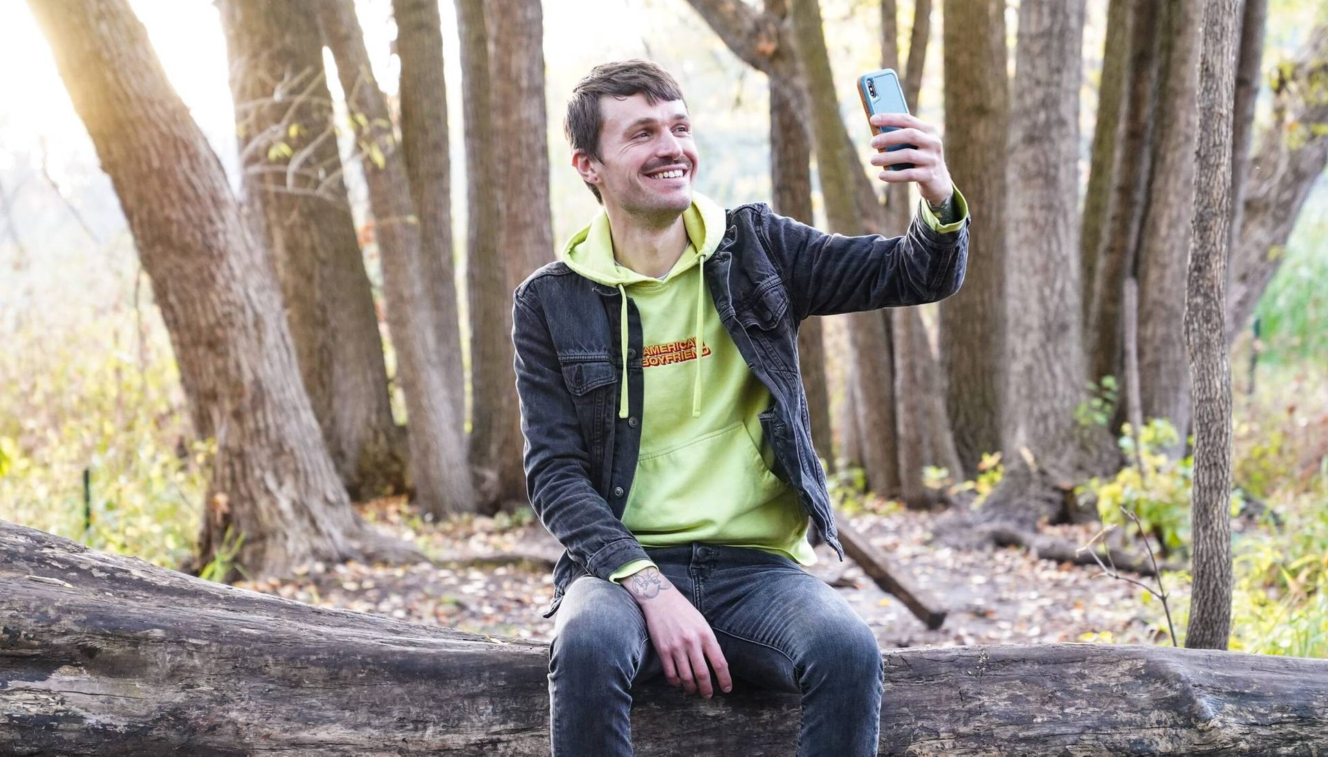 A smiling man sits on a log and holds up a smart phone to take a selfie