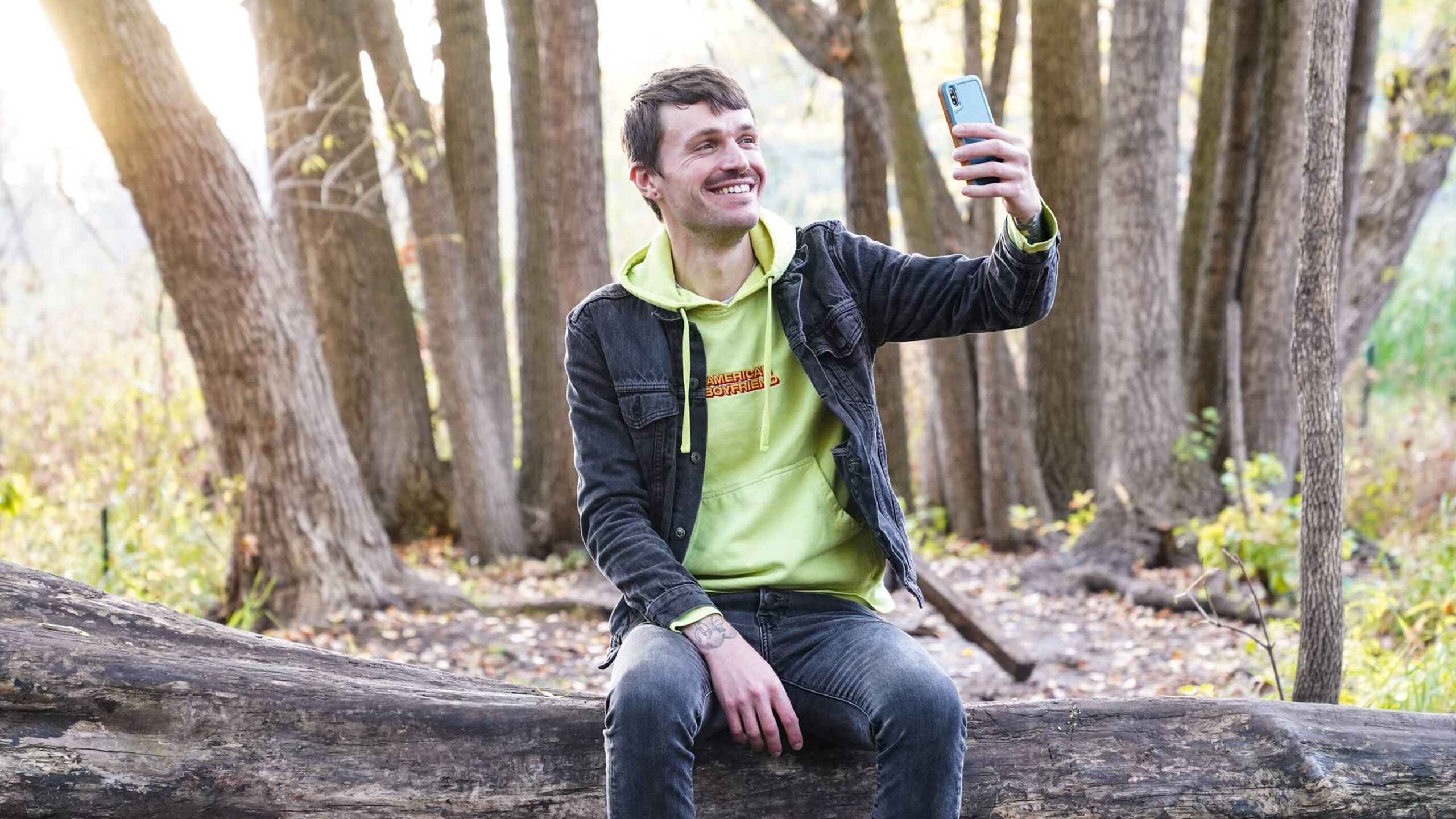 A smiling man sits on a log and holds up a smart phone to take a selfie, online lives, rewire