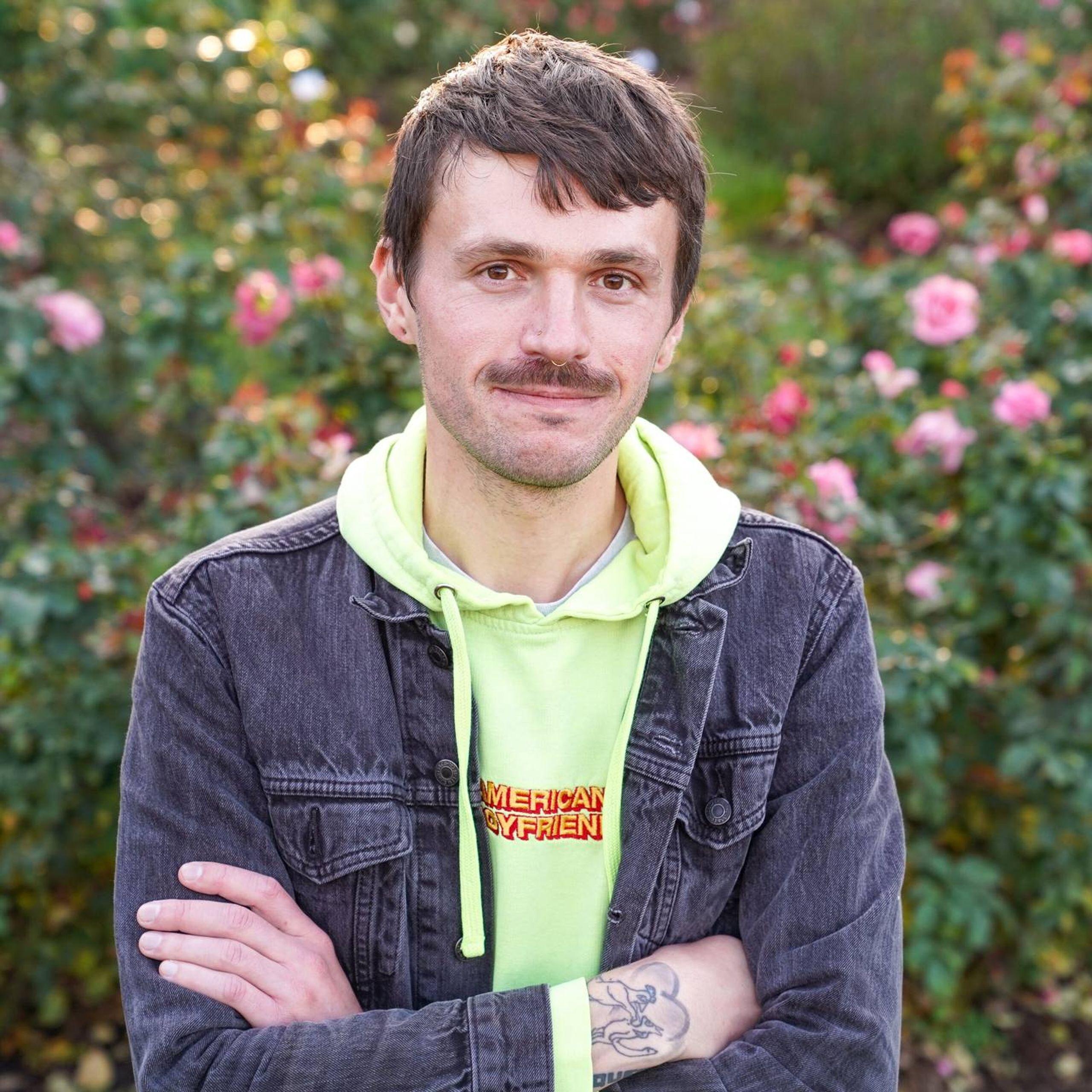 Portrait of a mustachioed man standing in a rose garden, online lives, rewire