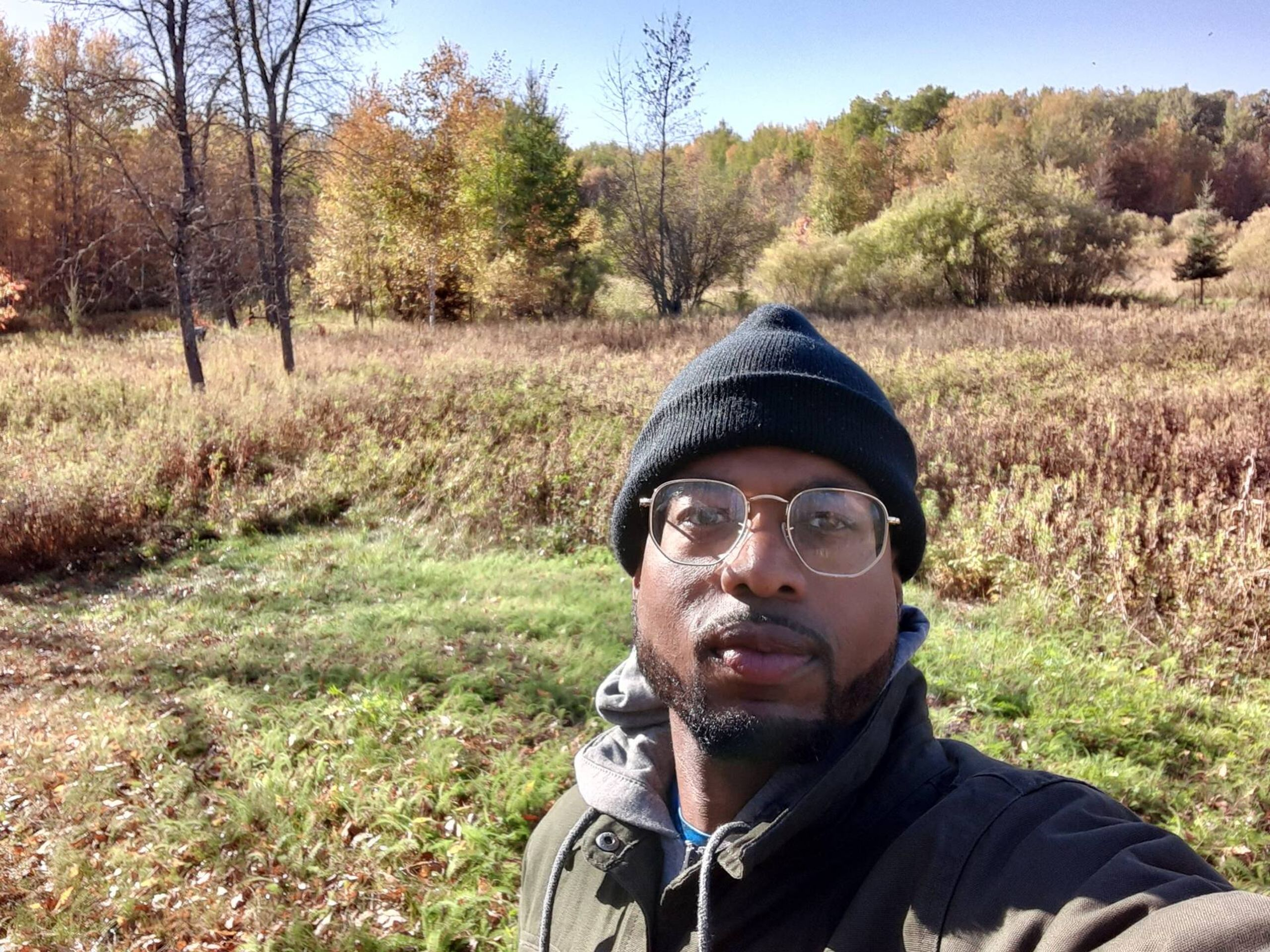 A selfie of Antonio Williams, a Black man, wearing glasses standing in a field. Rewire PBS Our Future Can't Vote