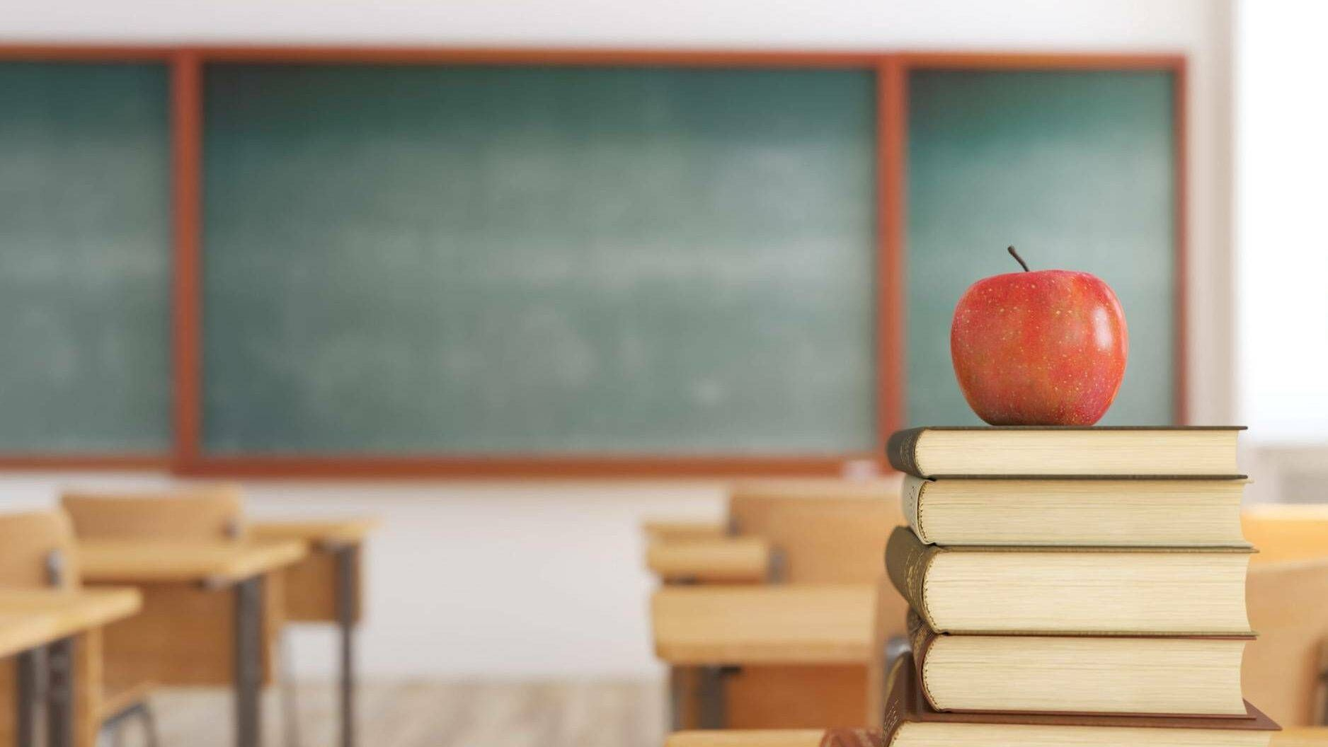 Photo of one red apple on top of books in an empty school classroom, Rewire, Public Schools
