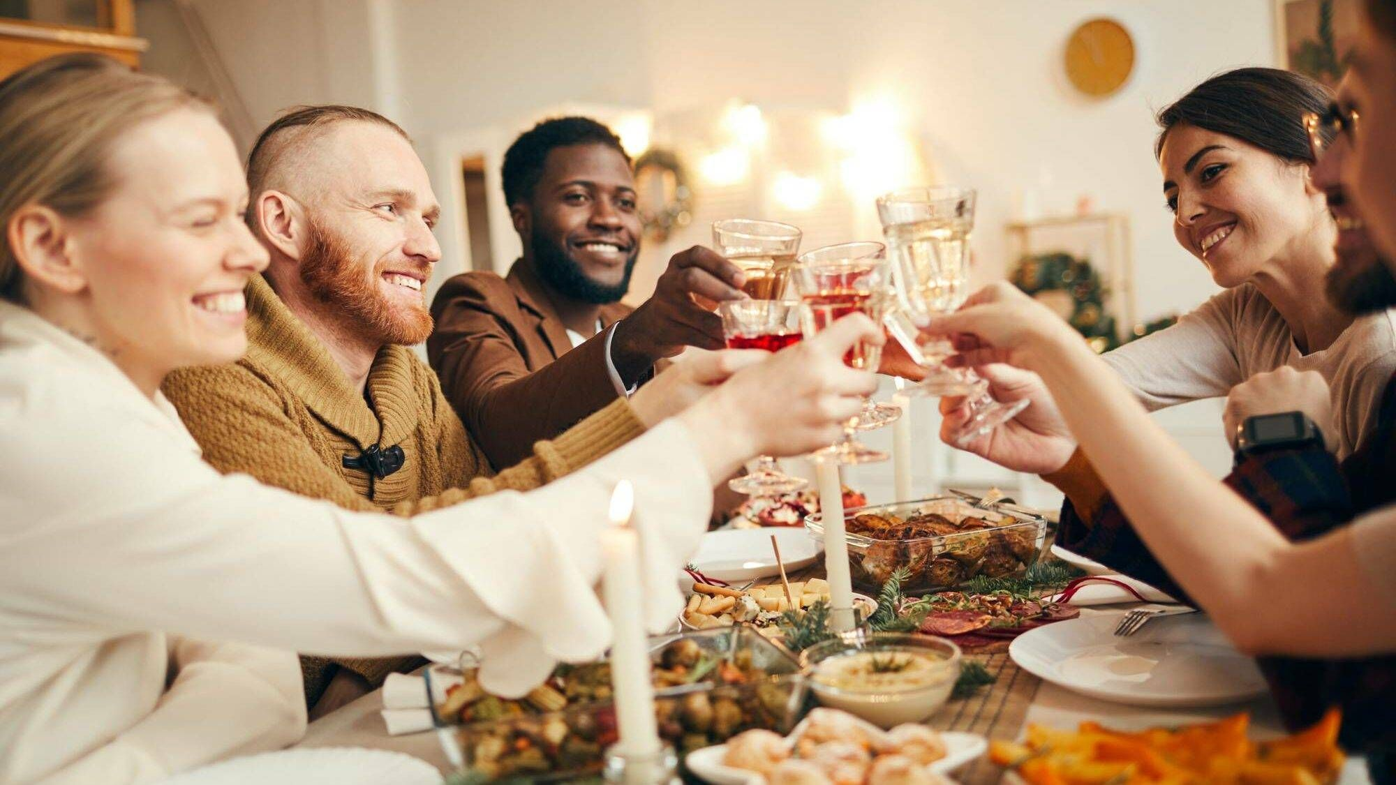 Multi-ethnic group of people raising glasses sitting at beautiful dinner table celebrating Christmas with friends and family, holidays, rewire