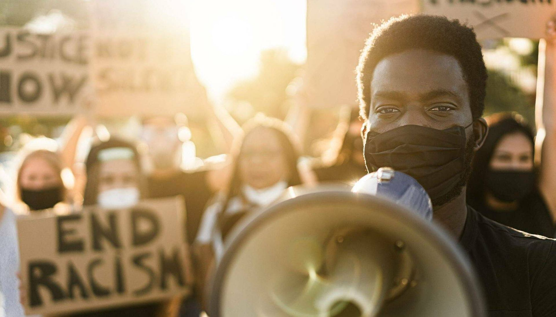 Protesters at a Black Lives Matter rally hold signs and megaphones in the street while wearing masks. Fighting for Black Lives Rewire PBS Our Future