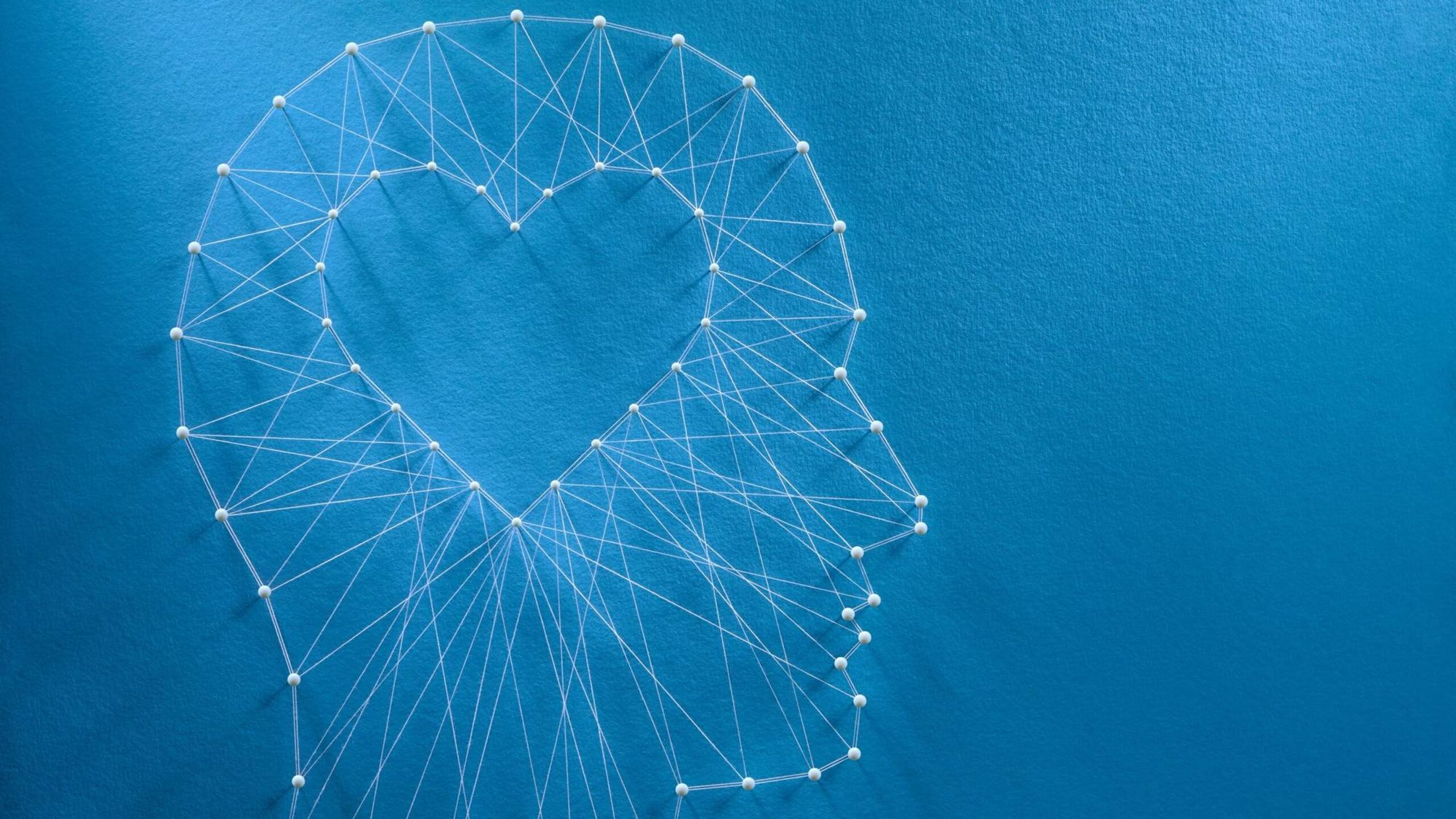 Network of pins and threads in the shape of a cut-out heart inside a human head symbolising that love is the core of our being and has its own logic. Emotional intelligence, Rewire