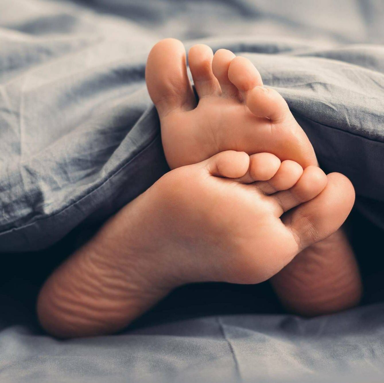 Photo of bare feet under a gray blanket in bed, mindful masturbation, self care