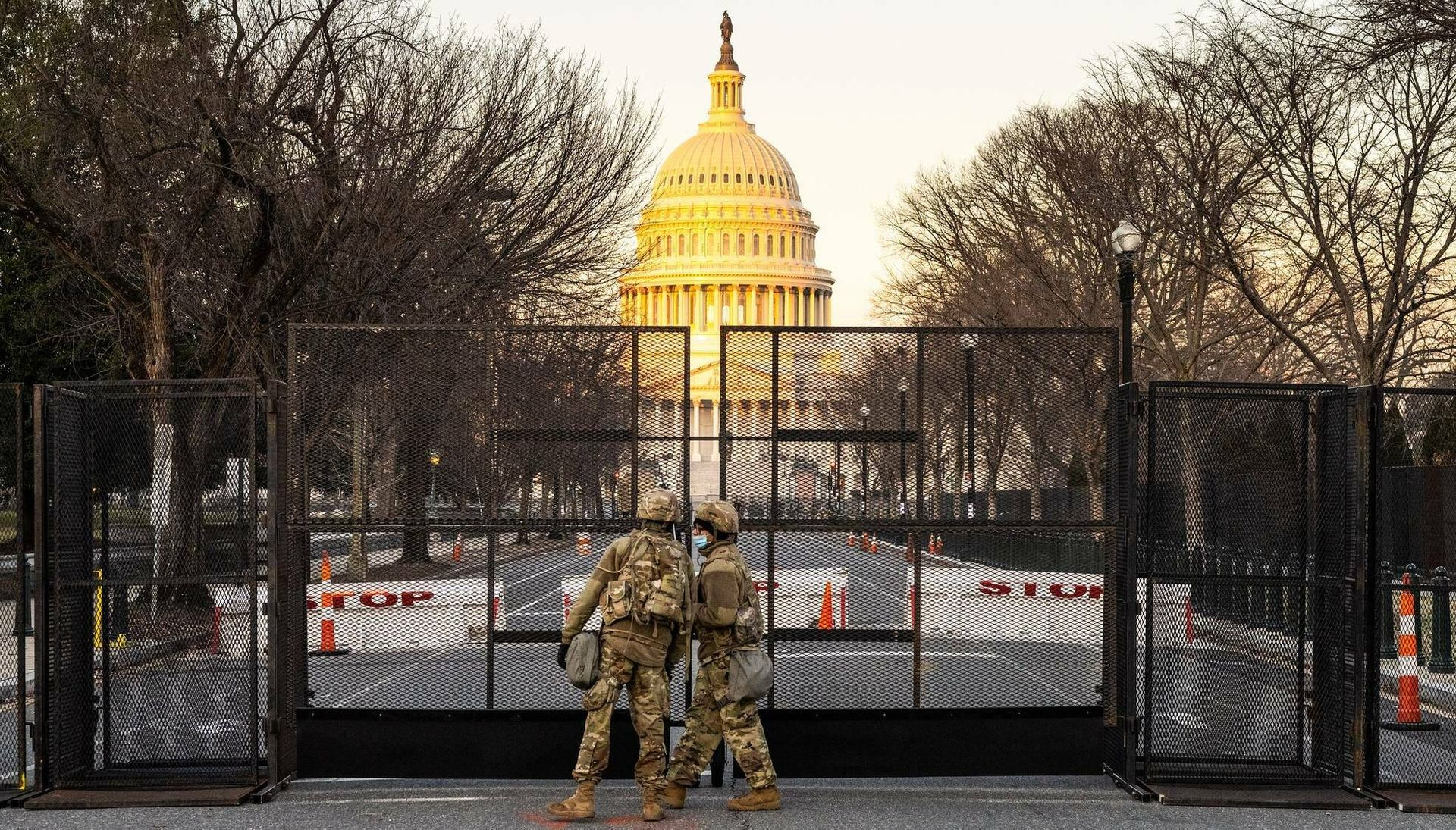 Two National Guard members stand in front of a fence surrounding the U.S. Capitol building in Washington, D.C.