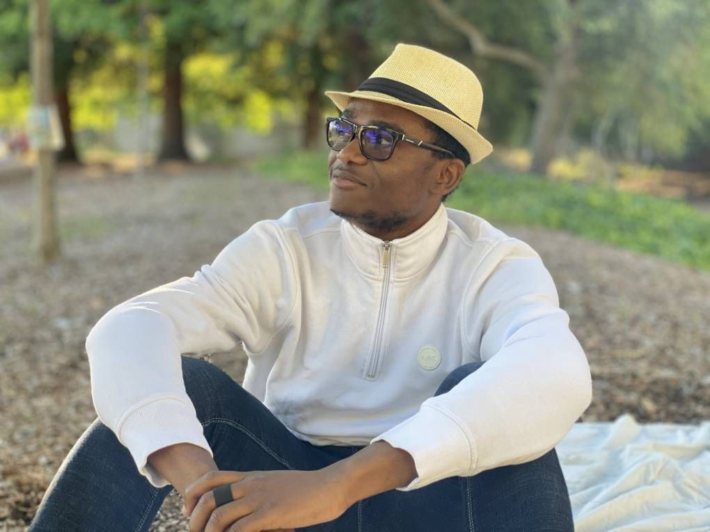 Student Abdoul Aziz Sandotin Coulibaly sits on the ground, looking off camera. Rewire PBS Our Future Berkeley
