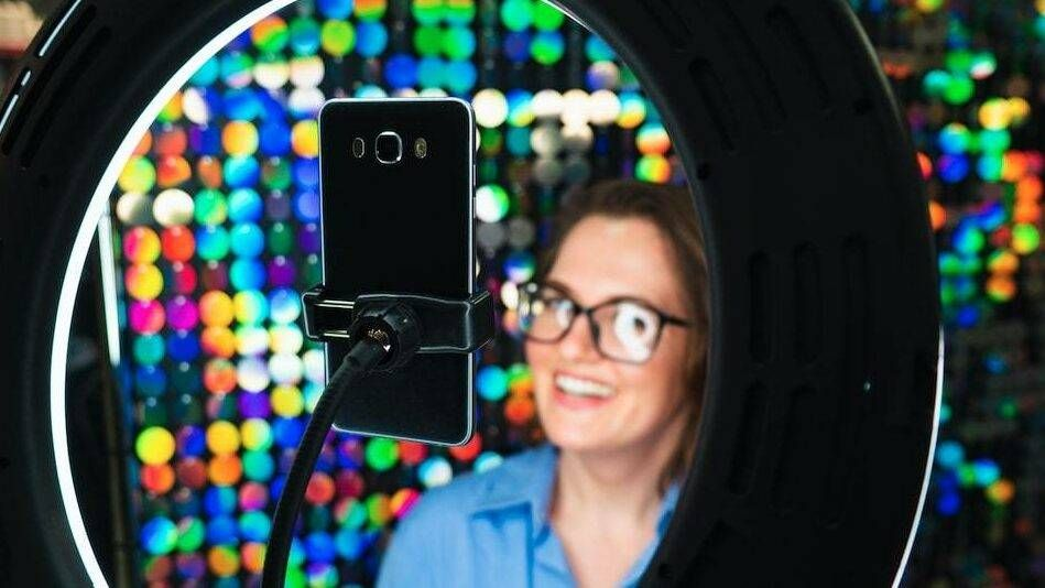 Photograph of a young woman, illuminated by a ring light, posing in front of a colorful background for a cell phone video, tik tok, future of job recruitment