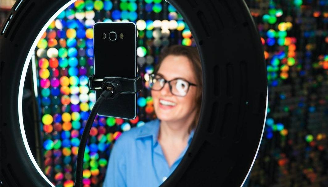 Photograph of a young woman, illuminated by a ring light, posing in front of a colorful background for a cell phone video