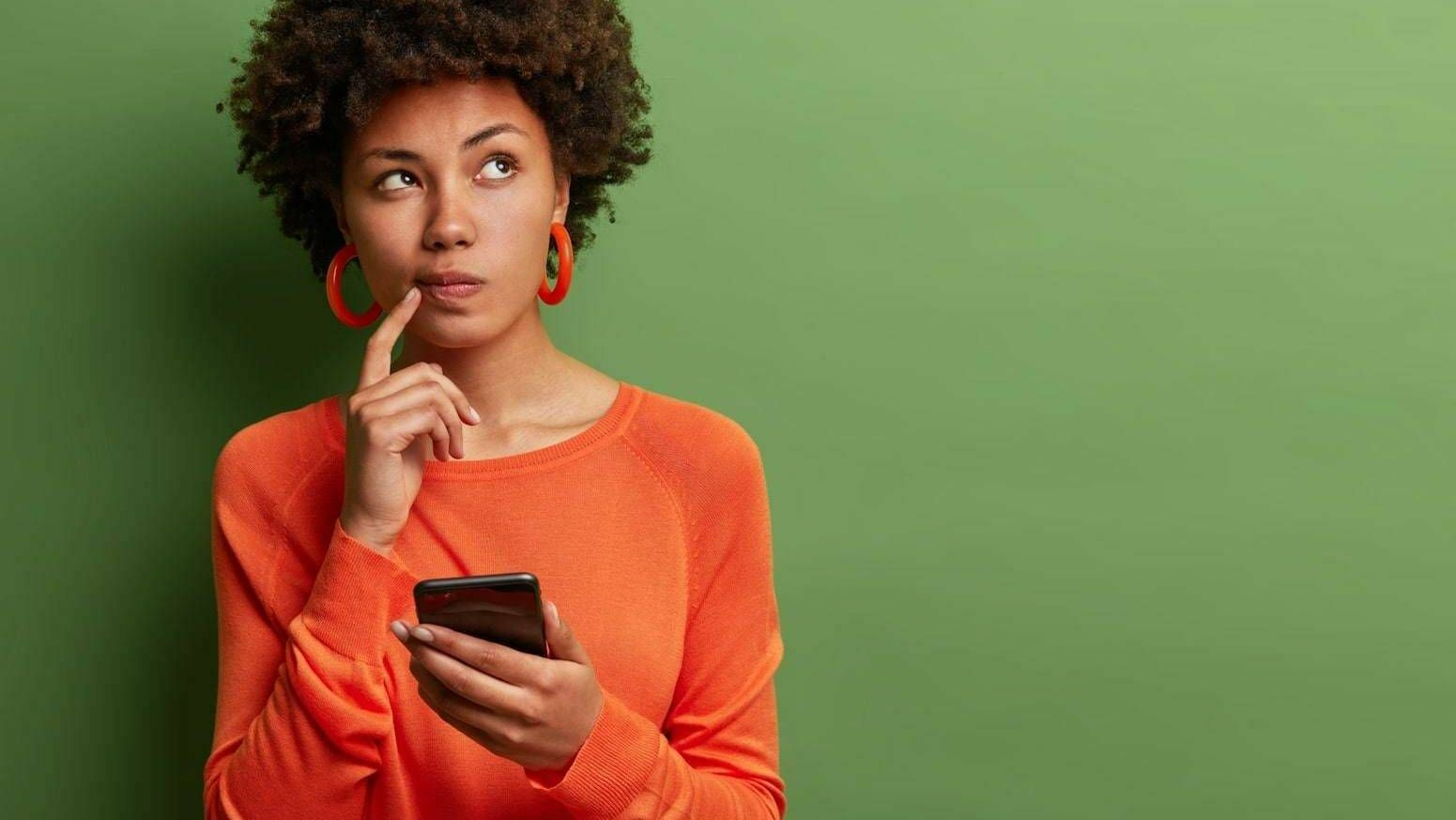 Photo of woman holding a smart phone with an inquisitive look on her face, rewire, social media at work