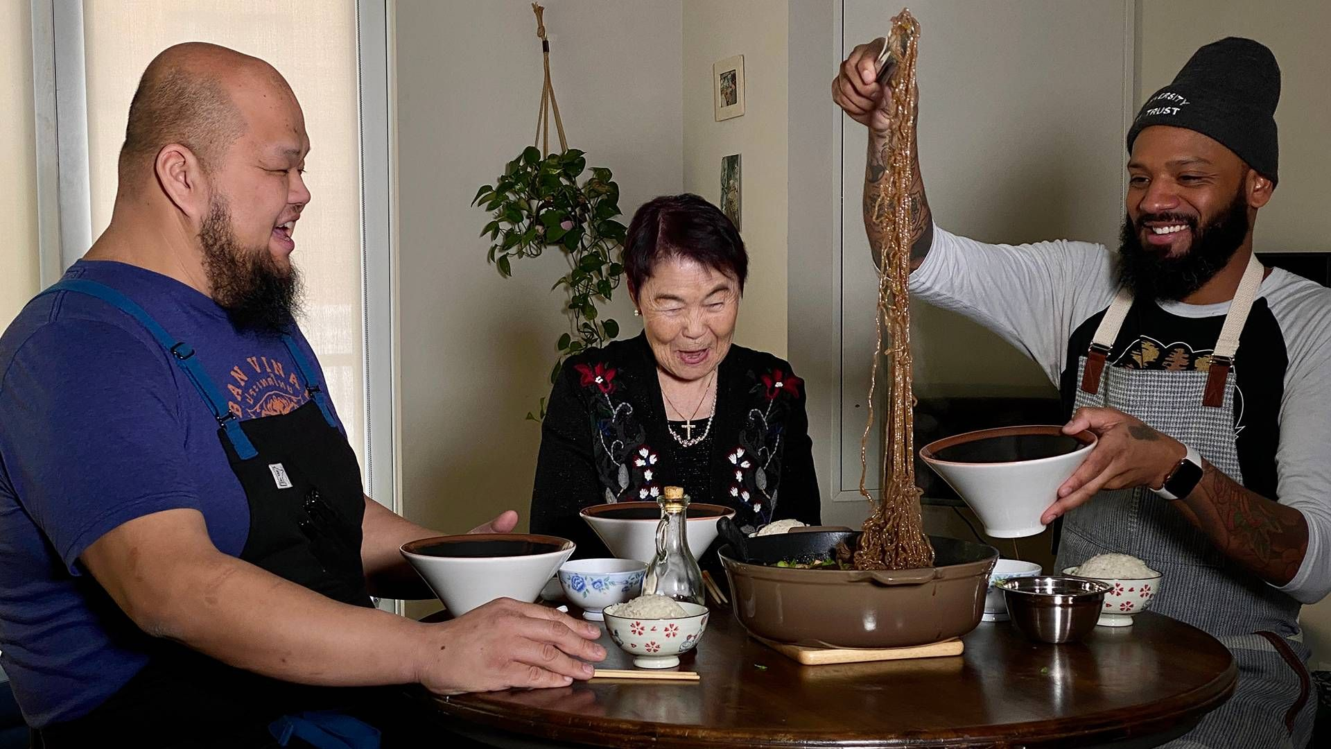 Chef Yia Vang, chef Justin Sutherland and Sutherland's grandmother sit around a table while Sutherland pulls noodles from a bowl. Rewire PBS Living one-pot meals
