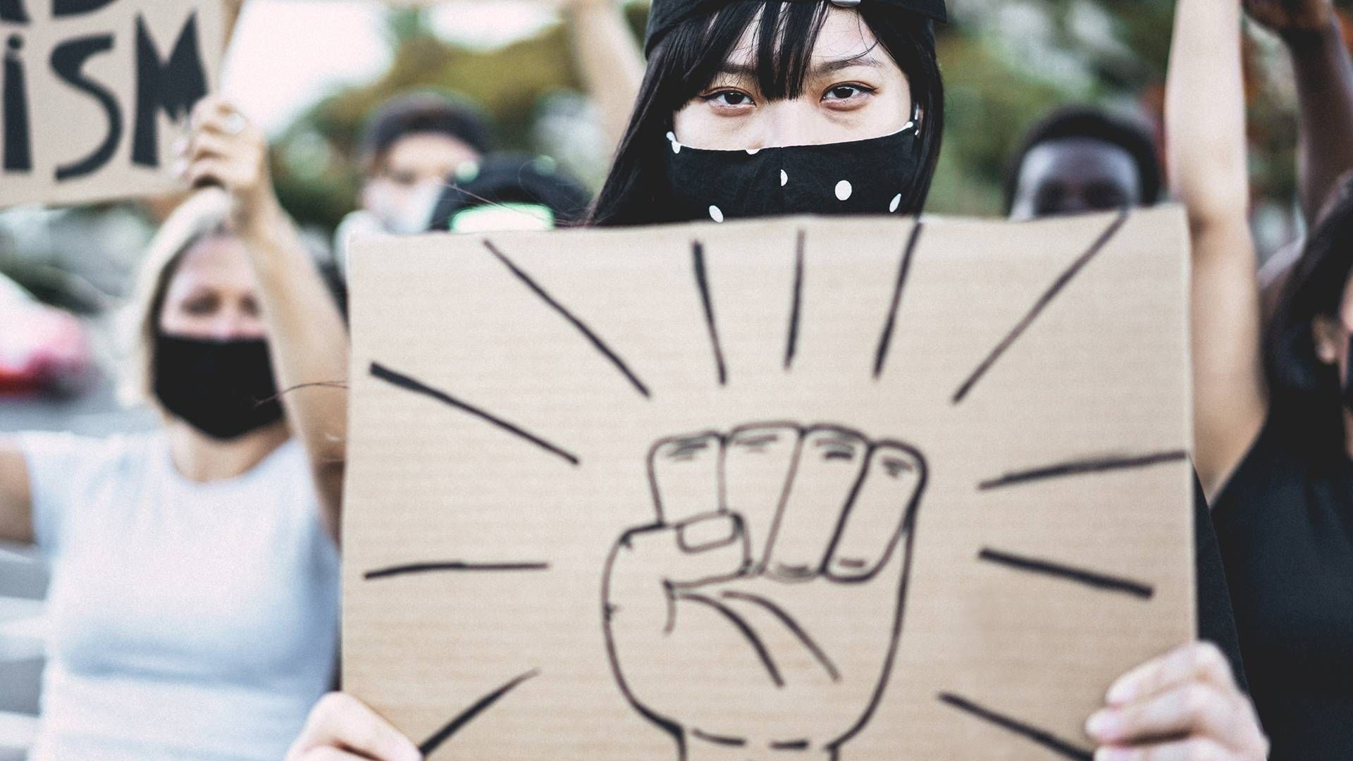 Asian girl wearing face mask while protest against racism on city street - Equal rights and demonstration concept - Focus on eyes