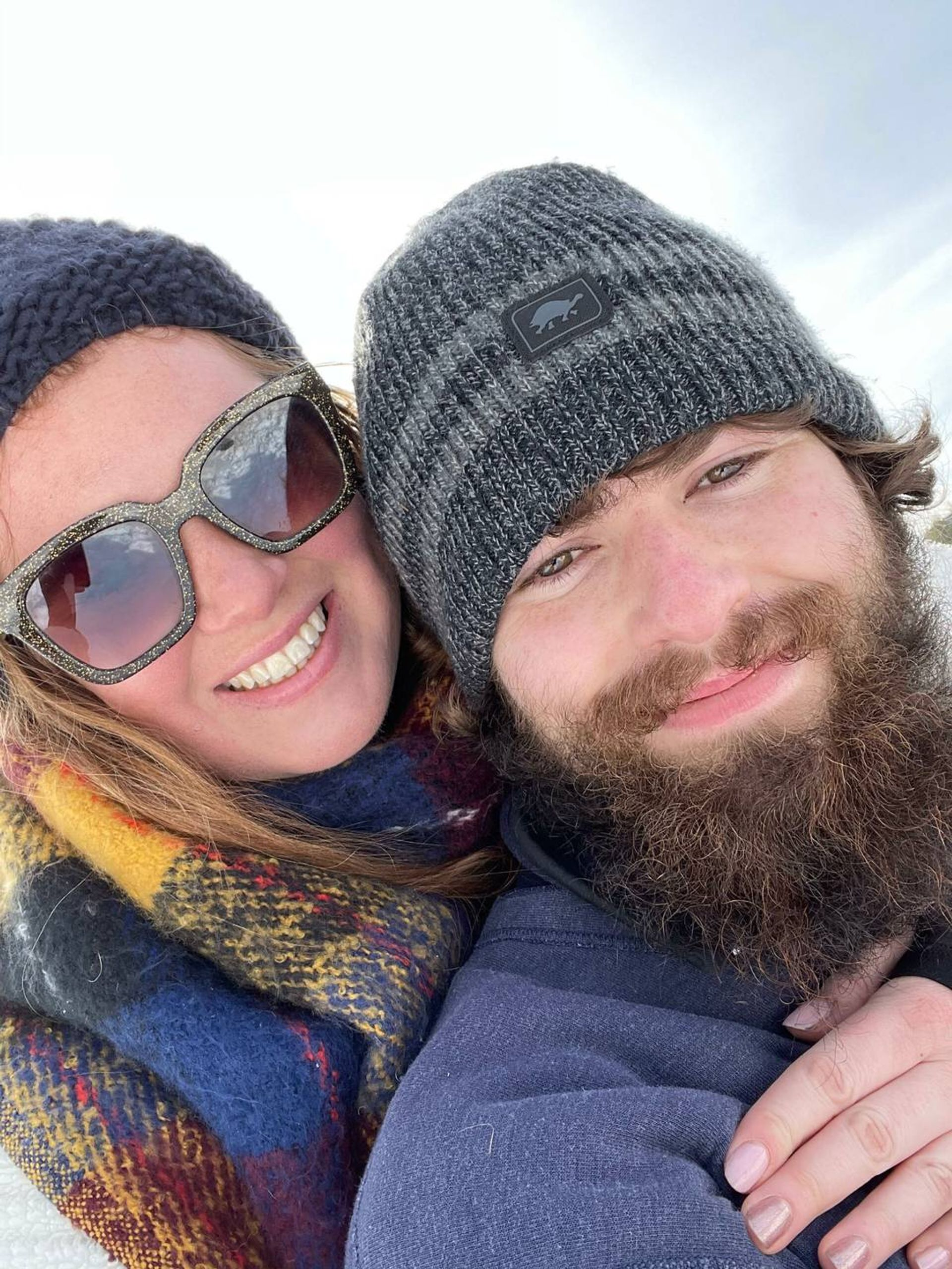 Photograph of a young couple in winter clothing who are looking at the camera and smiling. Age gap, love, Rewire, PBS