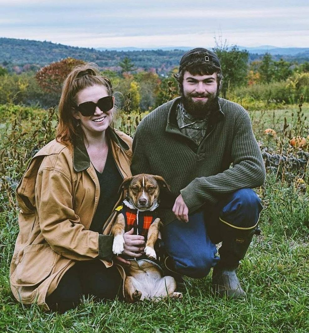 Photograph of a young couple kneeling with a small dog on green grass with hills in the background. Age gap, love, Rewire, PBS