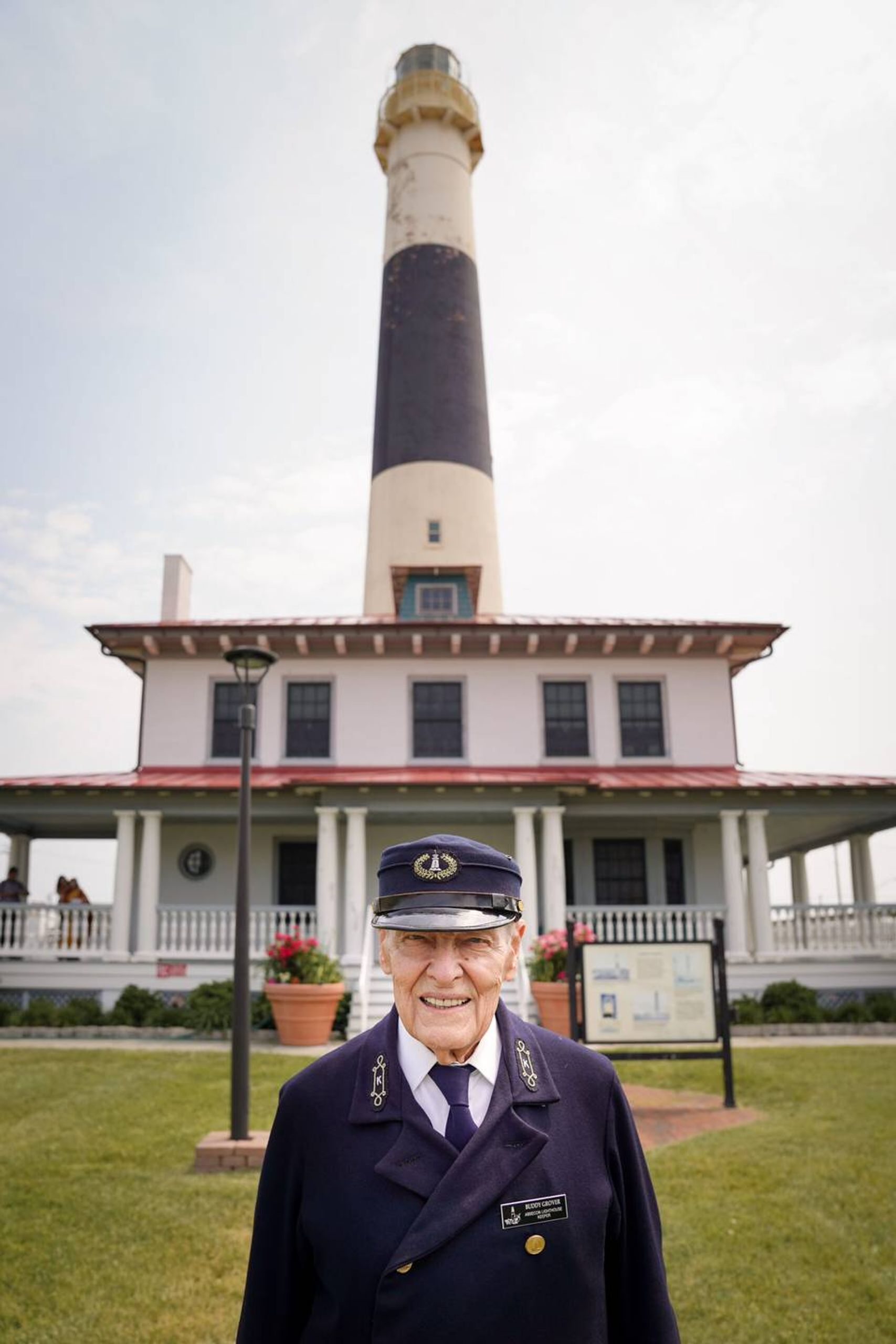 Photo of an older man in a blue uniform and hat, standing in front of a lighthouse. Life, elders, Rewire, PBS, our future