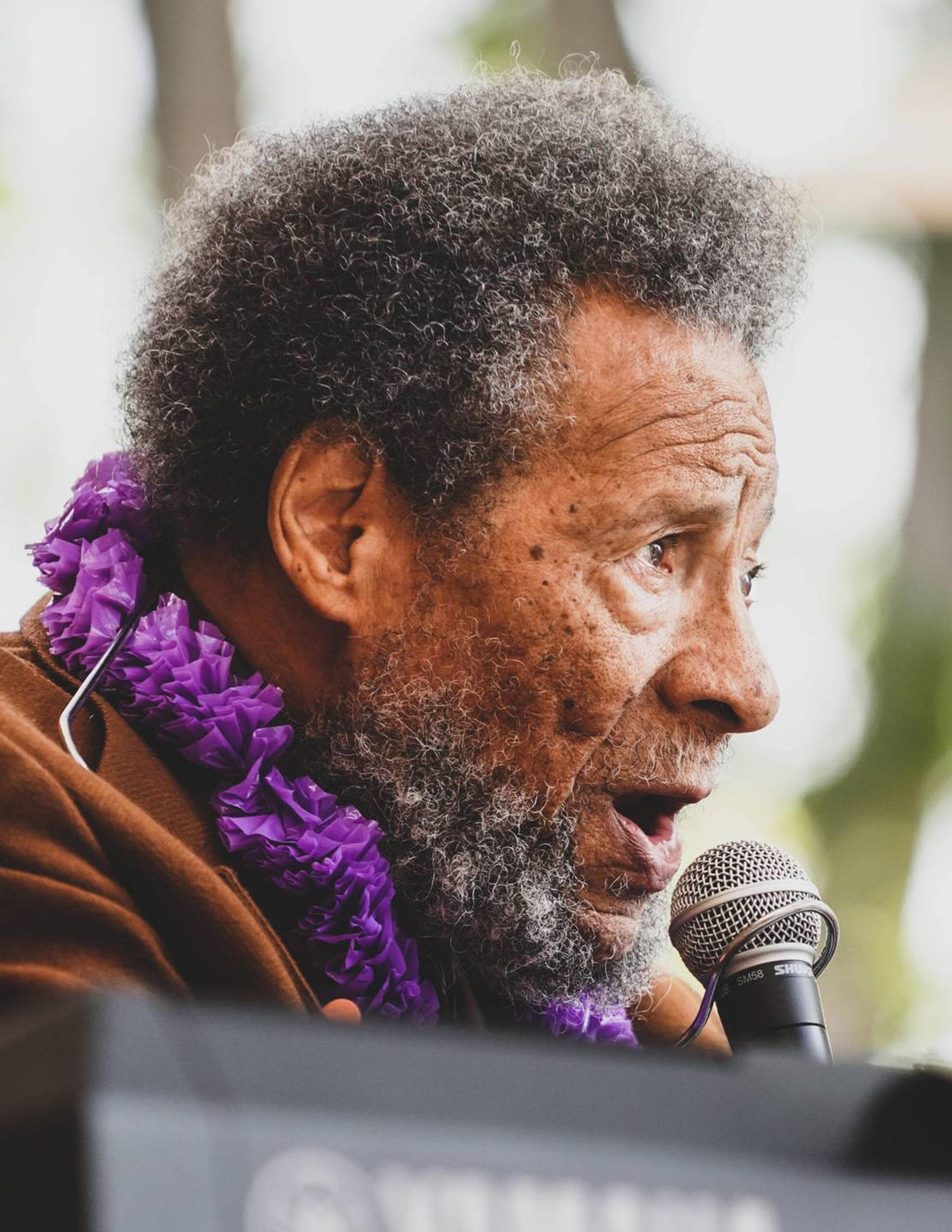 Photo of an older man sitting at a keyboard while wearing a purple lei and singing into a microphone. Life, elders, Rewire, PBS, our future