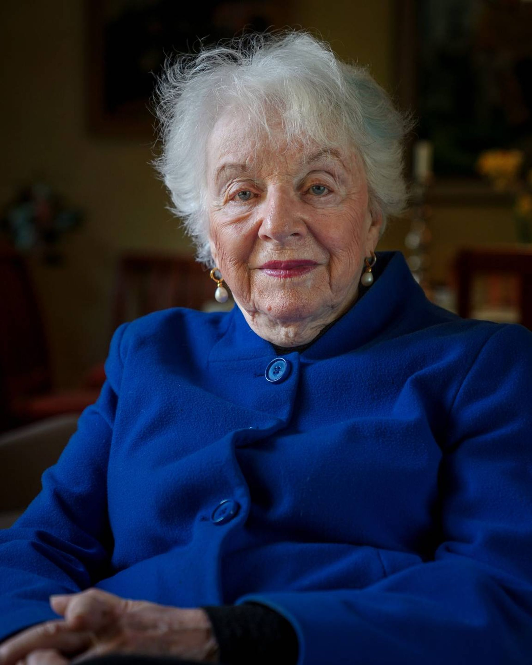 Photographic portrait of an older woman sitting on a couch in her home and smiling while wearing a blue blazer. Life, elders, Rewire, PBS, our future