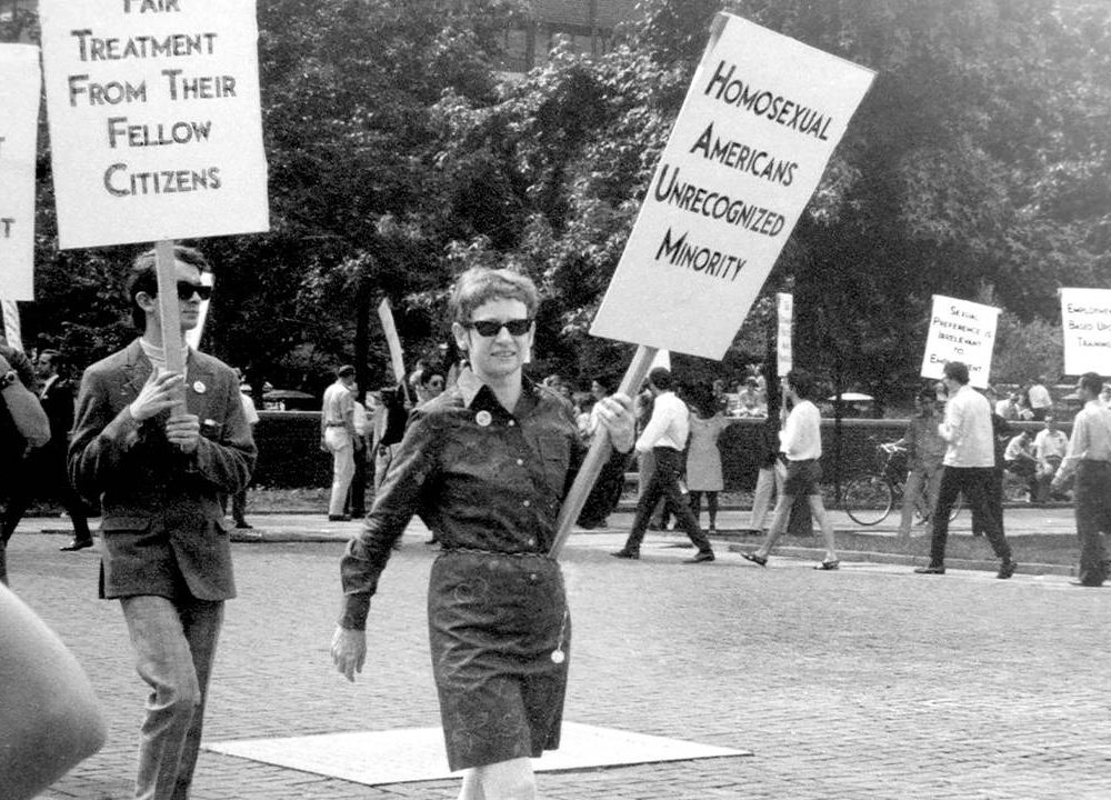An old photograph of LGBTQ activists marching with signs. 'CURED' documentary, Rewire, PBS