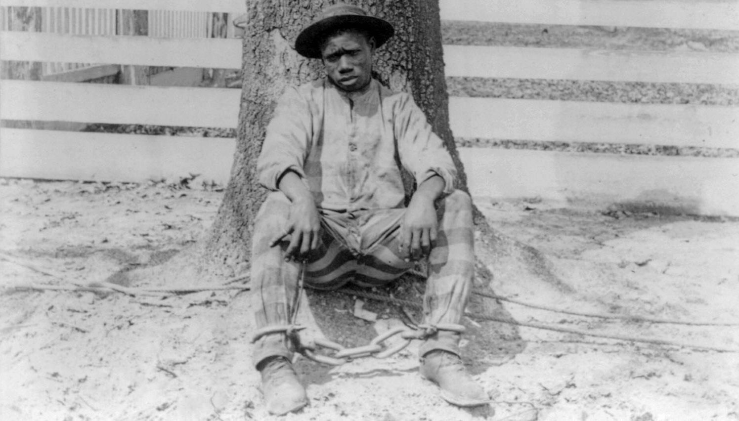 Black and white image of a Black man sitting against a tree, wearing a prison uniform and shackles. Slavery by Another Name, PBS, Rewire, our future,