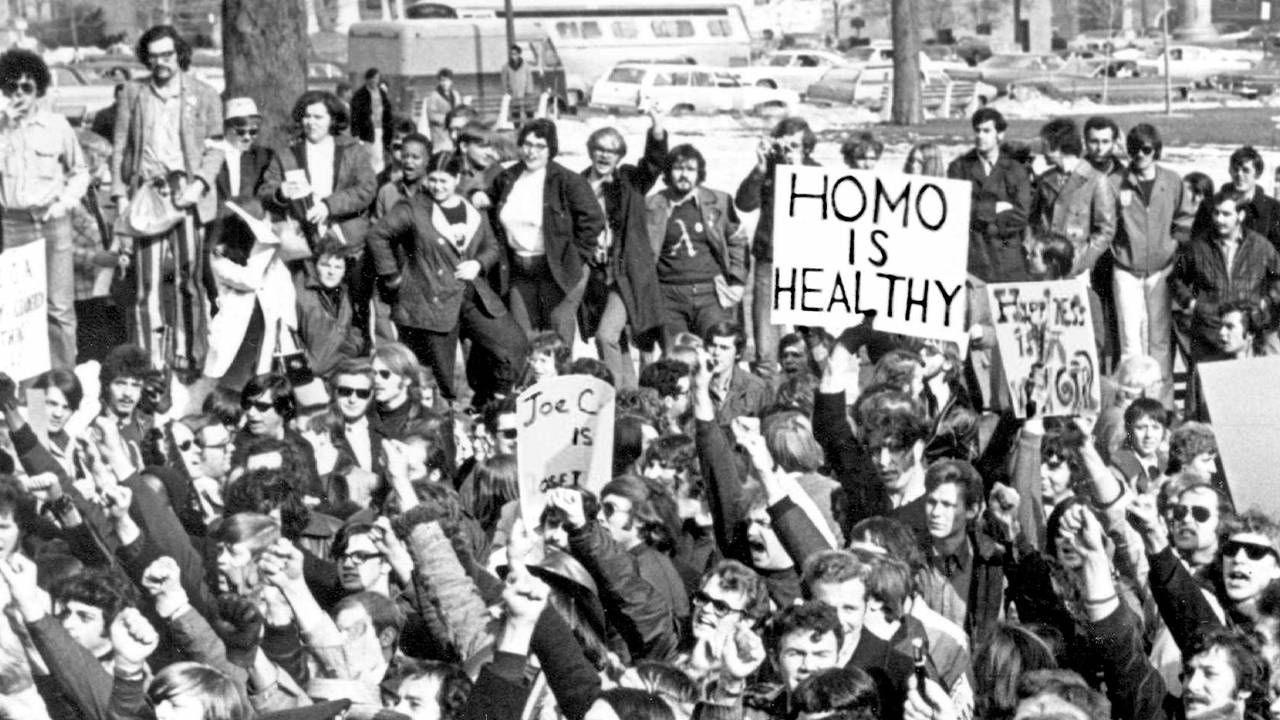 An old photograph of a group of LGBTQ activists. Rewire, PBS, Cured